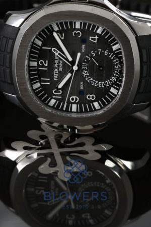 Patek Philippe Aquanaut Travel Time.Ref 5164A-0011. Case diameter 40.8mm. Water resistant to 120 metres. Automatic PP movement caliber 324 S C FUS. 29 Jewels, 294 parts, 28,800 VPH, power reserve 35-45 hours. Dual time zone mechanism indicating local and home time. Local and home day/night indications in apertures. Black embossed dial with white Arabic hour markers, luminous hands and outer minute track hour markers, date sub dial at the 6 o'clock position, central second sweep. Sapphire crystal see through case back, tropical rubber strap with double folding clasp. Box and extraxt from the archives, dated September 2012 RRP £27,090